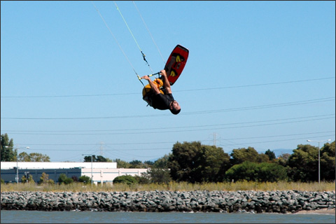 A kitesurfer, flipping across the bay.